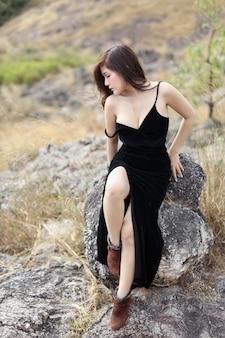 Junge asiatische frau in voller länge im schwarzen kleid, das draußen in der natur sitzt