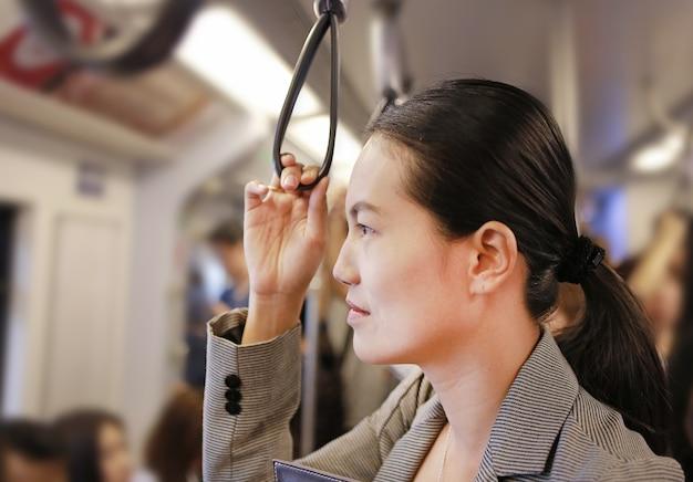 Junge asiatische frau innerhalb bts (bangkok-massentransit-system), die öffentlichen transportmittel