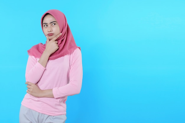 Junge asiatische frau isoliert auf blauem hintergrund, die nach denkender idee und zweifelhaftem ausdruck sucht