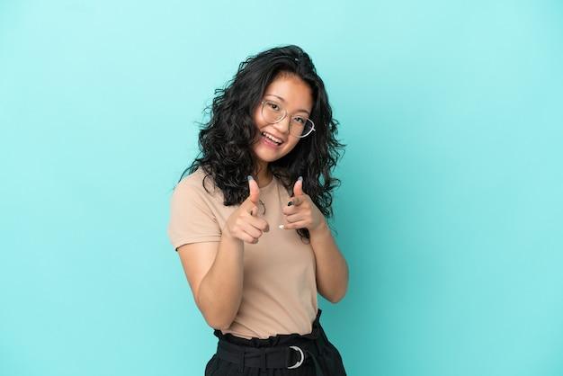 Junge asiatische frau isoliert auf blauem hintergrund, die nach vorne zeigt und lächelt