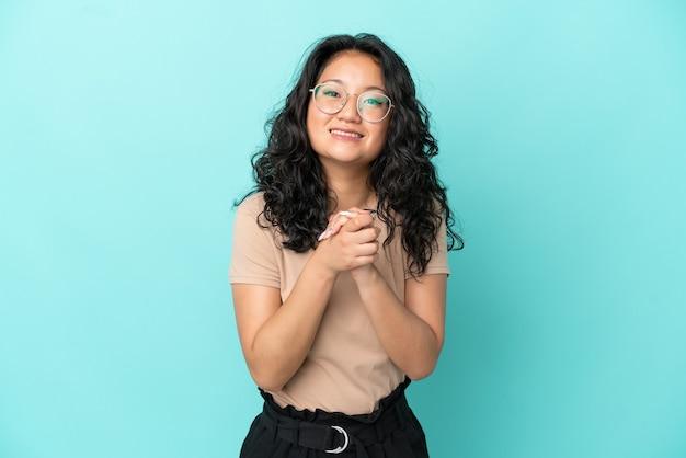 Junge asiatische frau isoliert auf blauem hintergrund lachen