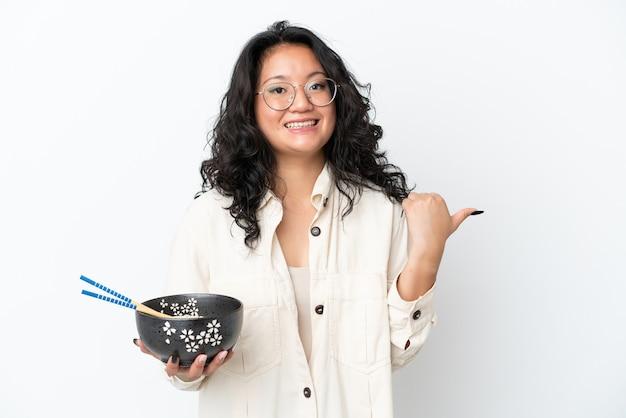 Junge asiatische frau isoliert auf weißem hintergrund, die auf die seite zeigt, um ein produkt zu präsentieren, während sie eine schüssel nudeln mit stäbchen hält