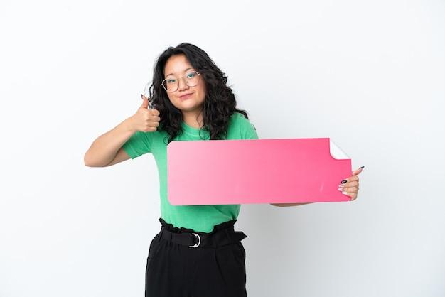 Junge asiatische frau isoliert auf weißem hintergrund, die ein leeres plakat mit dem daumen nach oben hält