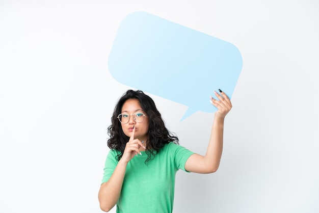 Junge asiatische frau isoliert auf weißem hintergrund, die eine leere sprechblase hält und stille-geste macht