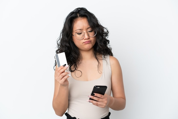 Junge asiatische frau isoliert auf weißem hintergrund, die mit dem handy mit einer kreditkarte kauft, während sie nachdenkt