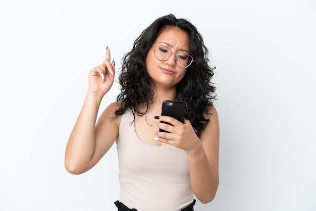 Junge asiatische frau isoliert auf weißem hintergrund mit handy und hebendem finger