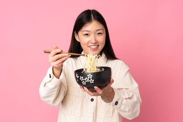Junge asiatische frau isoliert hält eine schüssel nudeln mit stäbchen und bietet es an