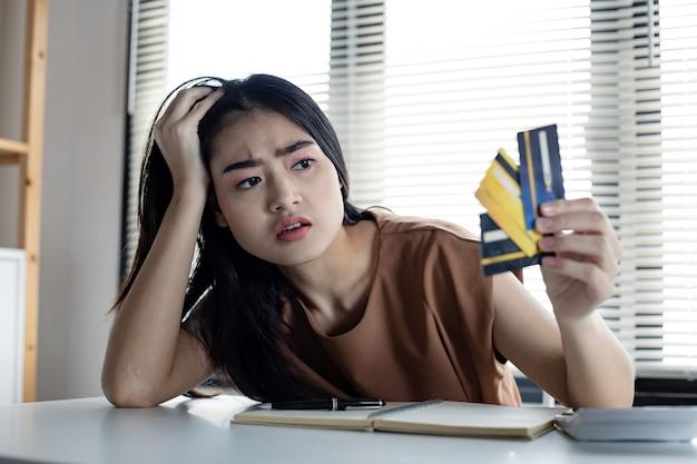 Junge asiatische frau ist gestresst und überlegt durch schulden von vielen kreditkarten. konzept des finanziellen problems. frauen fanden einen ausweg aus der verschuldung zur hand. müde von kreditkartenschulden.