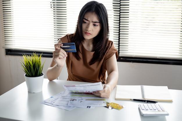 Junge asiatische frau ist gestresst und überlegt durch schulden von vielen kreditkarten und rechnungen. konzept des finanziellen problems. frauen fanden einen ausweg aus der verschuldung zur hand.