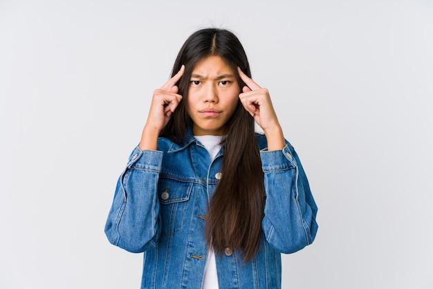 Junge asiatische frau konzentrierte sich auf eine aufgabe und hielt die zeigefinger, die kopf zeigen.