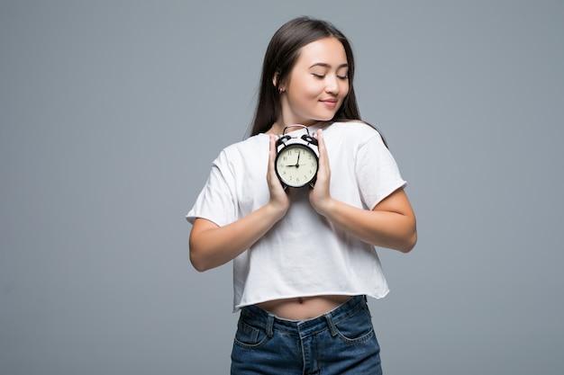 Junge asiatische frau lächeln mit einer uhr lokalisiert auf grauem hintergrund