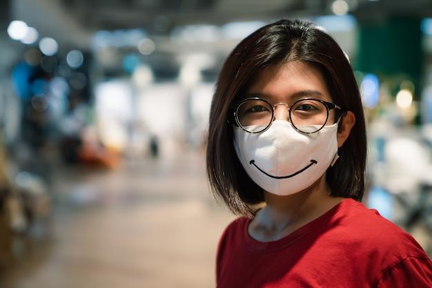 Junge asiatische frau lächelnd, die brillen und gesichtsmaske mit kopienraum trägt