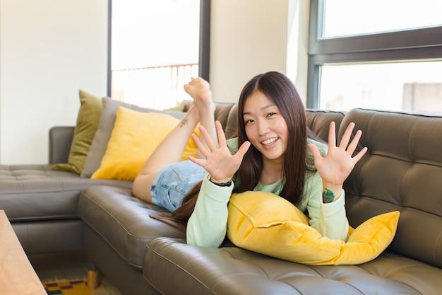 Junge asiatische frau lächelnd und freundlich aussehend, zeigt nummer zehn oder zehntel mit der hand nach vorne, countdown