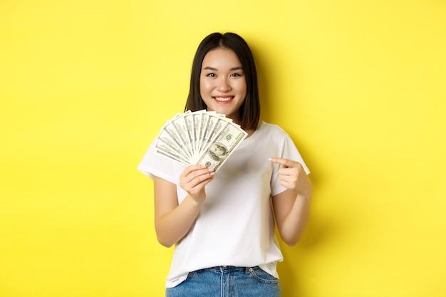 Junge asiatische frau lächelt, zeigt preisgeld, zeigt mit dem finger auf dollar, steht über gelbem hintergrund