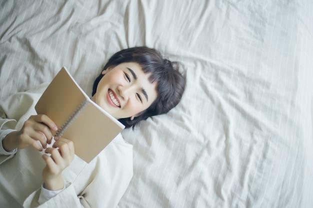 Junge asiatische frau liest ein buch im schlafzimmer.