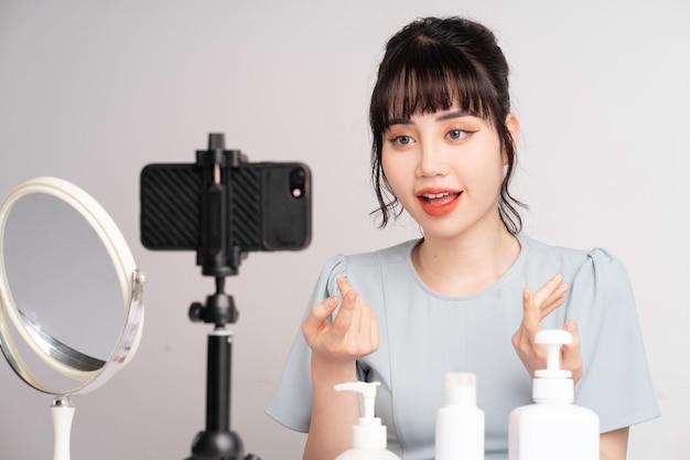 Junge asiatische frau live-streaming zum unterrichten make-up online