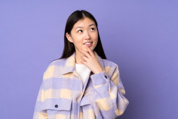 Junge asiatische frau lokalisiert auf lila, die beim lächeln nach oben schaut