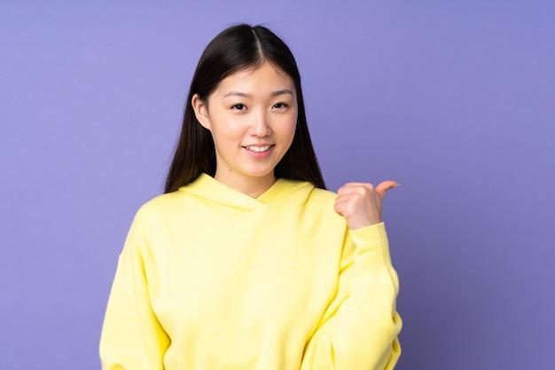 Junge asiatische frau lokalisiert auf lila hintergrund, der zur seite zeigt, um ein produkt zu präsentieren