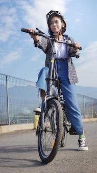 Junge asiatische frau macht eine pause mit dem fahrrad, bevor sie zur arbeit geht