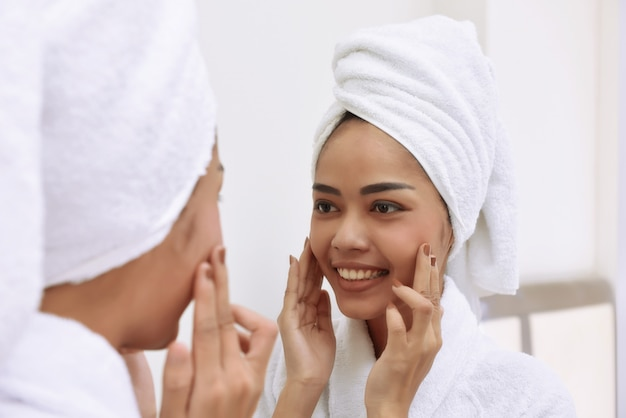 Junge asiatische frau mit badtüchern säubert ihr gesicht