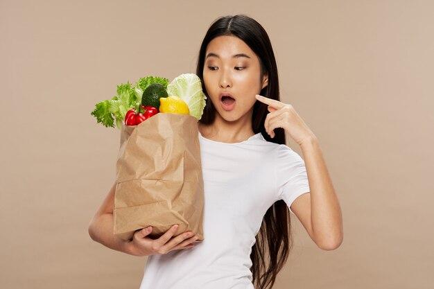 Junge asiatische frau mit beutel des gemüses