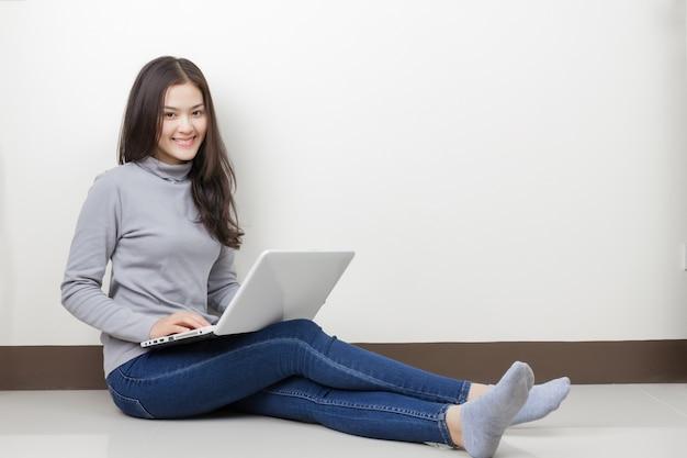 Junge asiatische frau mit brille und laptop, die im raum sitzen. glückliches smileygesicht.