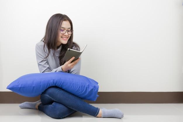 Junge asiatische frau mit brillenhand, die notizbuch hält, das im raum sitzt. glückliches smileygesicht.