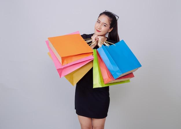 Junge asiatische frau mit bunten einkaufstüten