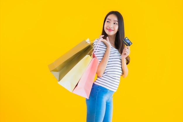 Junge asiatische frau mit bunter einkaufstasche