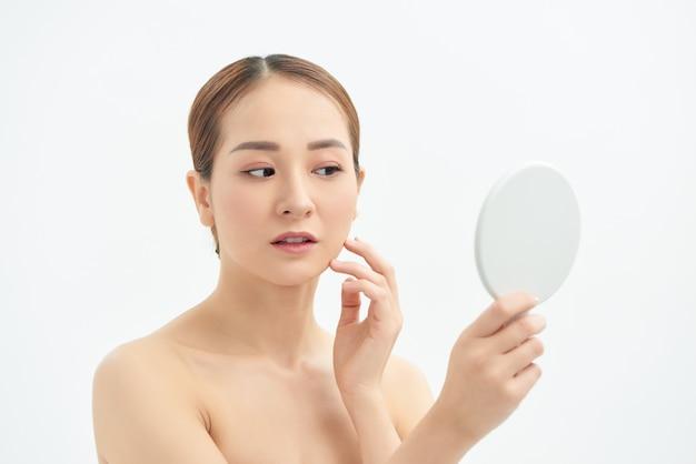 Junge asiatische frau mit dem problemgesicht, das den spiegel über weißem hintergrund betrachtet.