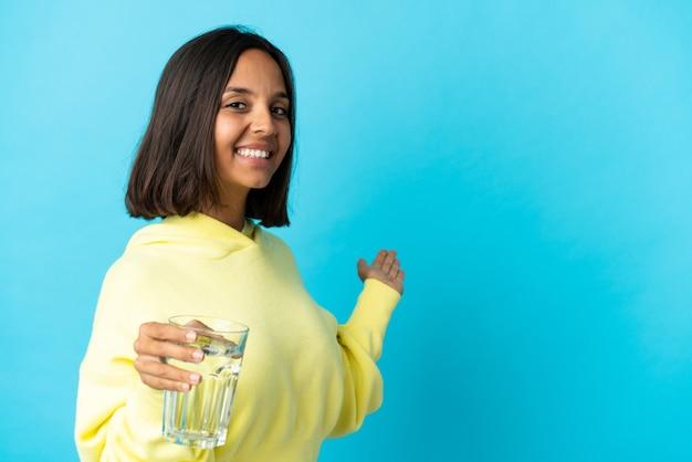 Junge asiatische frau mit einem glas wasser lokalisiert auf blau verlängerten händen zur seite für die einladung zu kommen