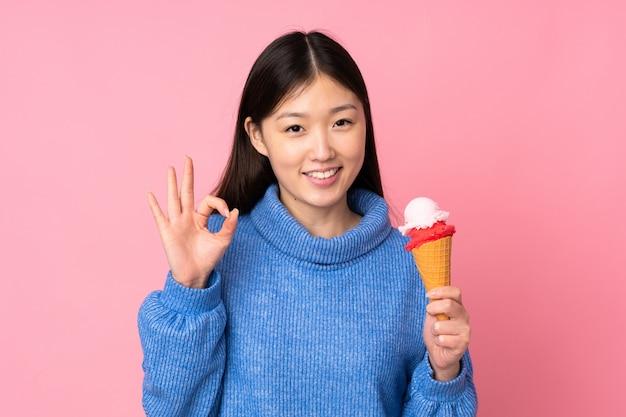 Junge asiatische frau mit einem kornetteis lokalisiert auf rosa wand, die ok zeichen mit den fingern zeigt