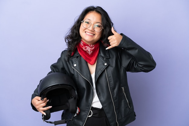 Junge asiatische frau mit einem motorradhelm auf lila hintergrund isoliert, die telefongeste macht. ruf mich zurück zeichen