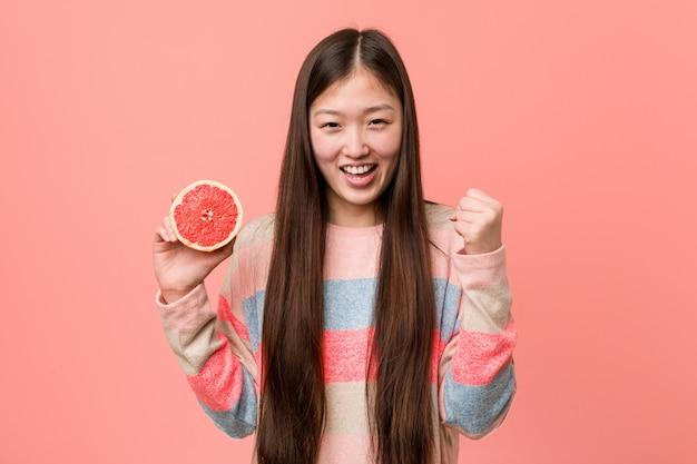 Junge asiatische frau mit einem pampelmusenzujubeln sorglos und aufgeregt. sieg-konzept.
