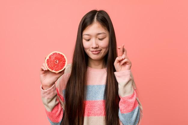 Junge asiatische frau mit einer grapefruit, die finger für glück kreuzt