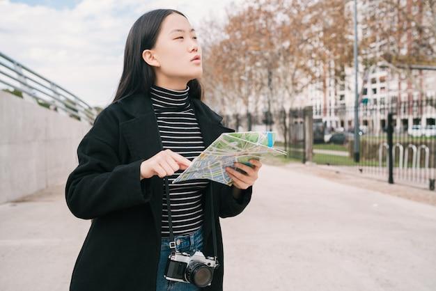 Junge asiatische frau mit einer karte.
