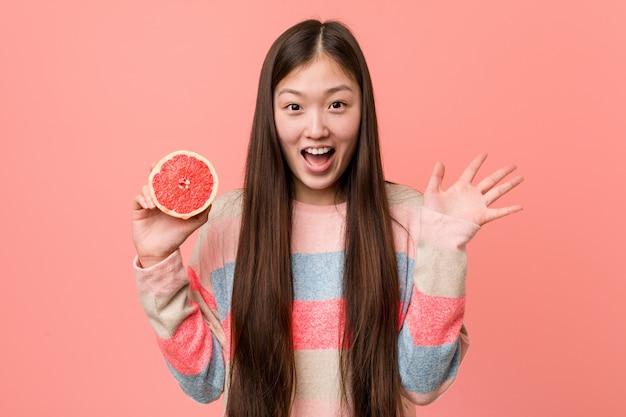 Junge asiatische frau mit einer pampelmuse einen sieg oder einen erfolg feiernd