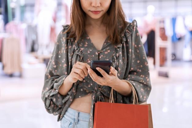 Junge asiatische frau mit einkaufstaschen unter verwendung des smartphones und des einkaufens am einkaufszentrum, frauenlebensstilkonzept