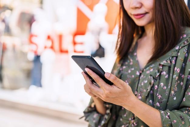 Junge asiatische frau mit einkaufstaschen unter verwendung des smartphones und des einkaufens am einkaufszentrum