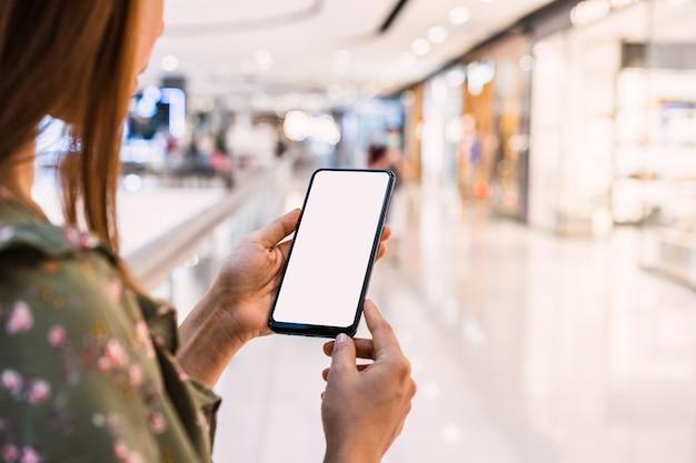 Junge asiatische frau mit einkaufstaschen unter verwendung des smartphones und des einkaufens im einkaufszentrum, frauenlebensstilkonzept