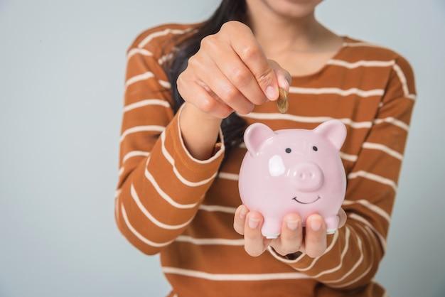 Junge asiatische frau mit geldmünze und sparschwein
