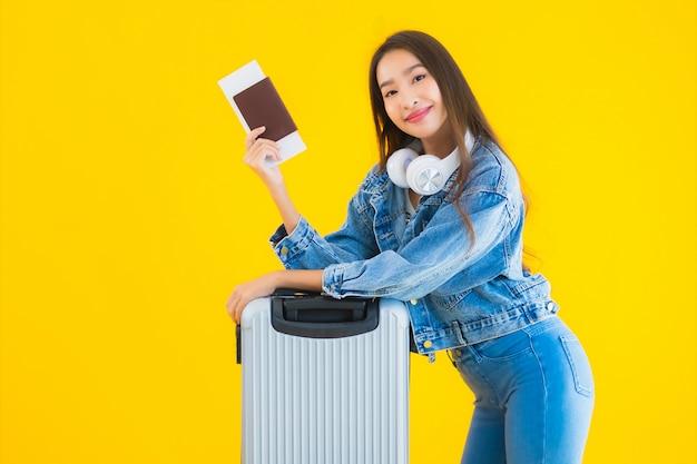 Junge asiatische frau mit gepäcktasche und reisepass