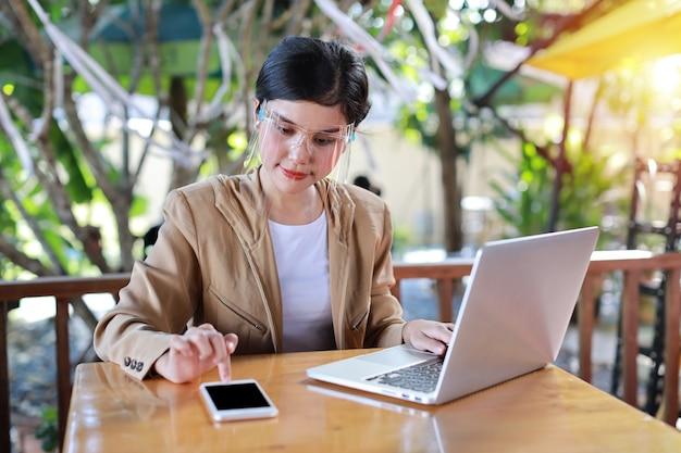 Junge asiatische frau mit gesichtsschutz, der im kaffeehaus sitzt und auf smartphone und auf laptop-computer arbeitet. neues normales und soziales distanzierungskonzept