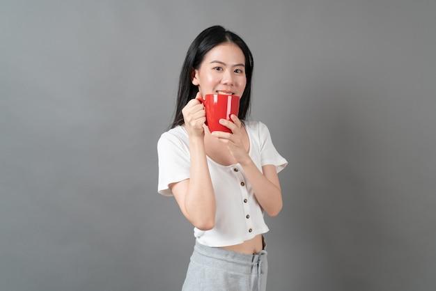 Junge asiatische frau mit glücklichem gesicht und hand, die kaffeetasse auf grauem hintergrund hält