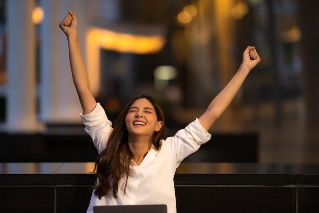 Junge asiatische frau mit glücklichem schreiendem überraschtem gesicht unter verwendung des laptops in einer stadt