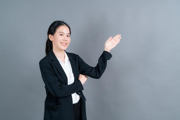 Junge asiatische frau mit hand, die auf seite präsentiert