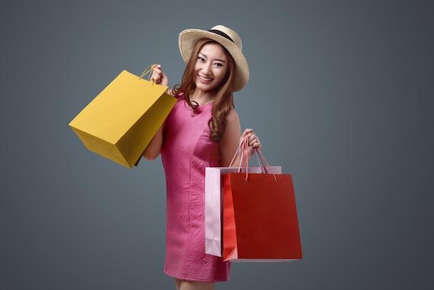 Junge asiatische frau mit hut und farbigen einkaufstaschen