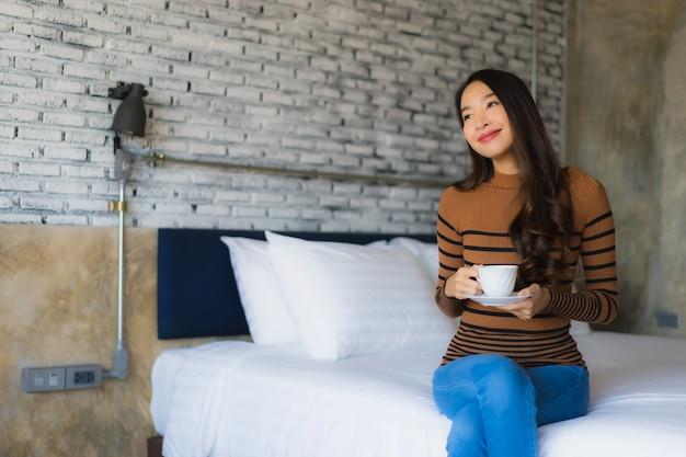 Junge asiatische frau mit kaffeetasse auf bett