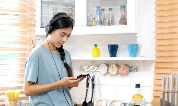 Junge asiatische frau mit kopfhörern hörend musik von der küche des handys zu hause