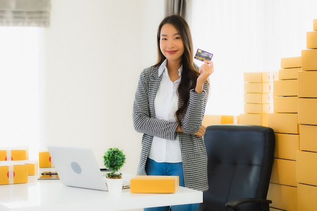 Junge asiatische frau mit kreditkarte und pappkarton